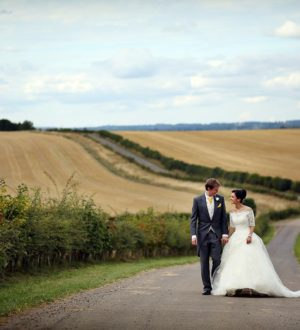 Couple walking the main drive at Clock Barn © Neale James Photography