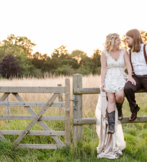 Bride and groom sat on a fence in Clock Barn © Lydia Stamps Photography