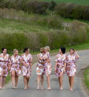 Bride and bridesmaids walking down the drive © Millard Photography