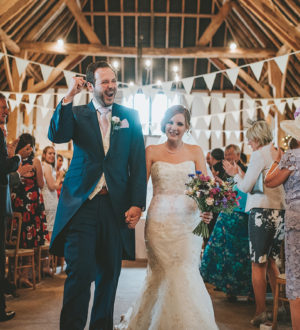 Bride and groom celebrating inside Clock Barn © Tom Halliday Photography