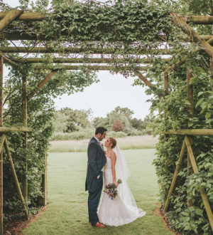 Couple under the archway in Clock Barn  © Tom Halliday Photography