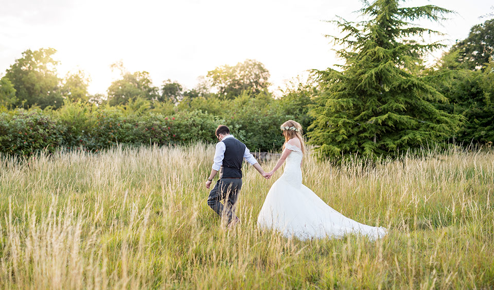 Bride and groom walking in the outdoor space at Clock Barn