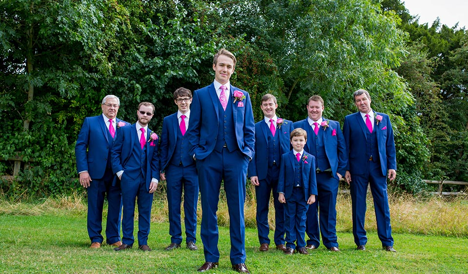 Michael and his groomsmen stand in the gardens at Clock Barn wearing their blue suits