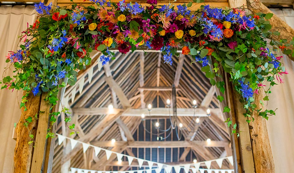 The doorway into the wedding reception barn is decorated with summer wedding flowers