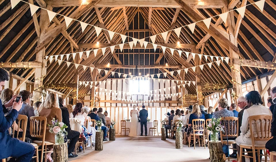 The exposed beams and pretty bunting make Clock Barn the perfect country wedding venue in Hampshire