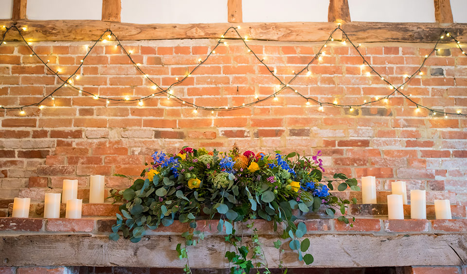The cosy snug at Clock Barn is decorated with faux candles and beautiful purple flowers and summer blooms