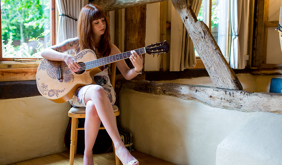 A woman plays the guitar providing wedding music for the couple's wedding day