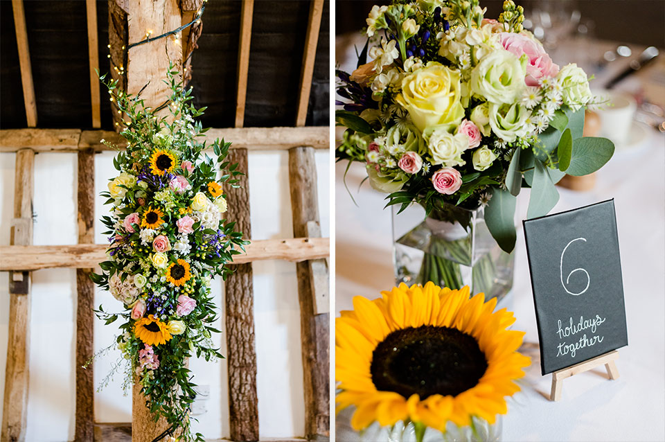 A huge arrangement of wedding flowers decorate some of the oak beams in the main barn – wedding ideas