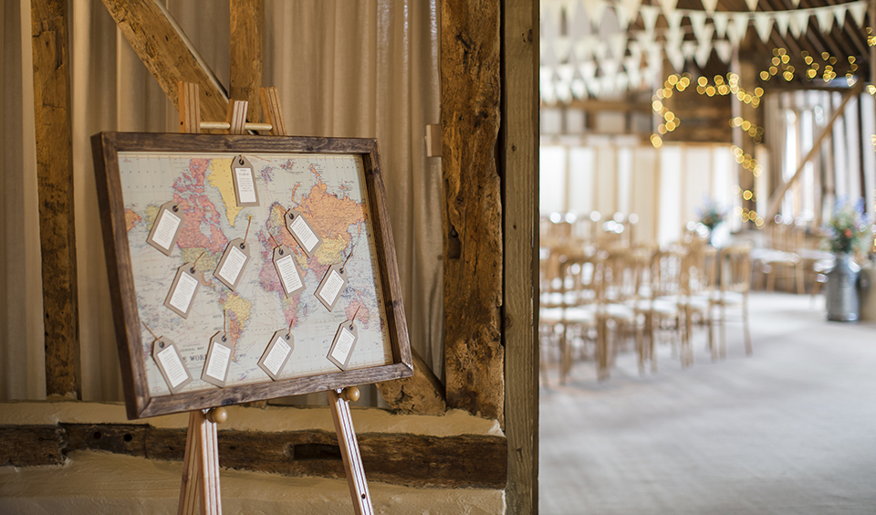 A travel wedding theme table plan stands outside the wedding ceremony barn