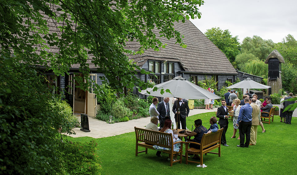 Guests enjoy a drinks reception in the pretty gardens of this Hampshire wedding venue