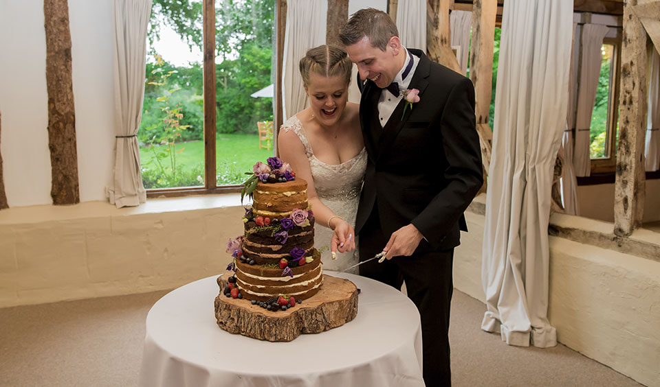 Together the bride and groom cut their naked wedding cake decorated with fresh fruit and purple flowers