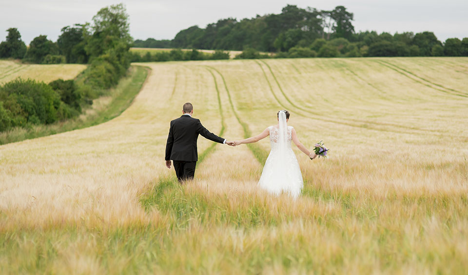 Abi and Chris hold hands as they stroll through the field – wedding barns Hampshire