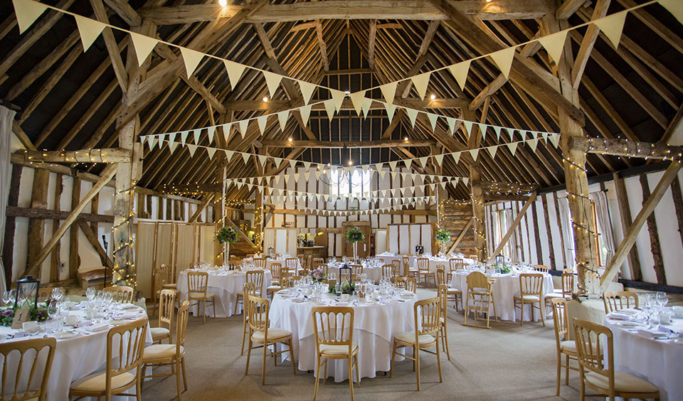 White bunting hangs across the wedding reception barn where guests will soon enjoy their wedding breakfast