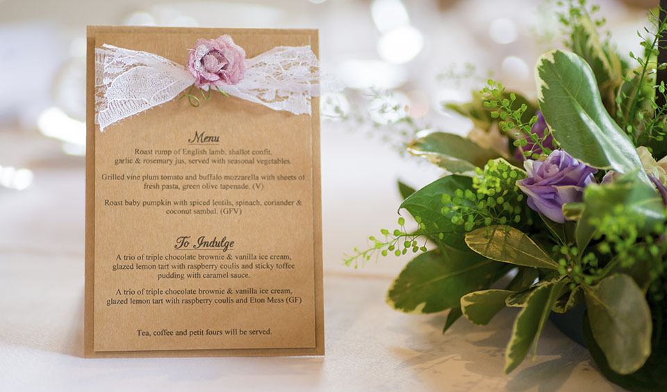 The couple's wedding menu is presented on brown card and decorated with white lace and a pink rose
