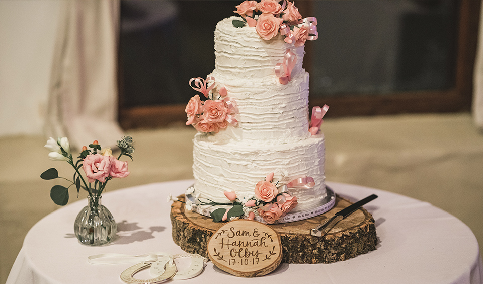 A three-tier wedding cake is covered in white butter cream icing and decorated with pink flowers