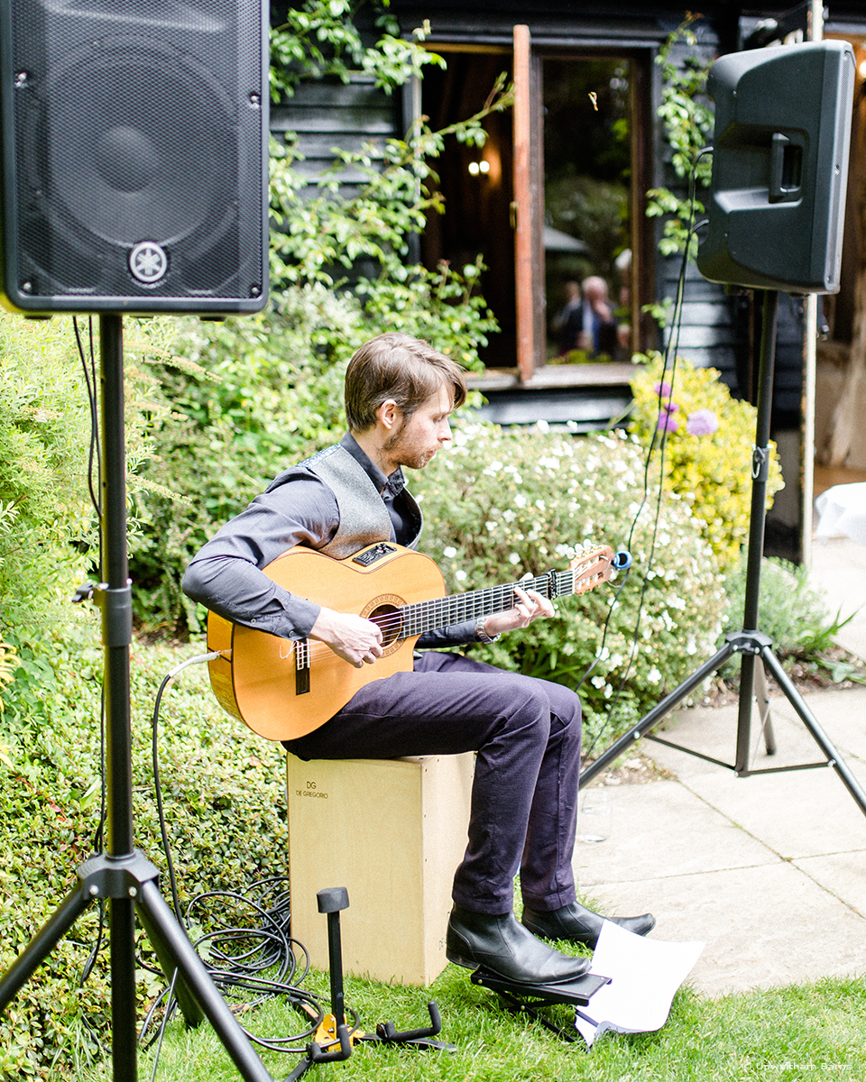Create a happy summer atmosphere with a live musician playing outside in the gardens of this beautiful Hampshire wedding barn