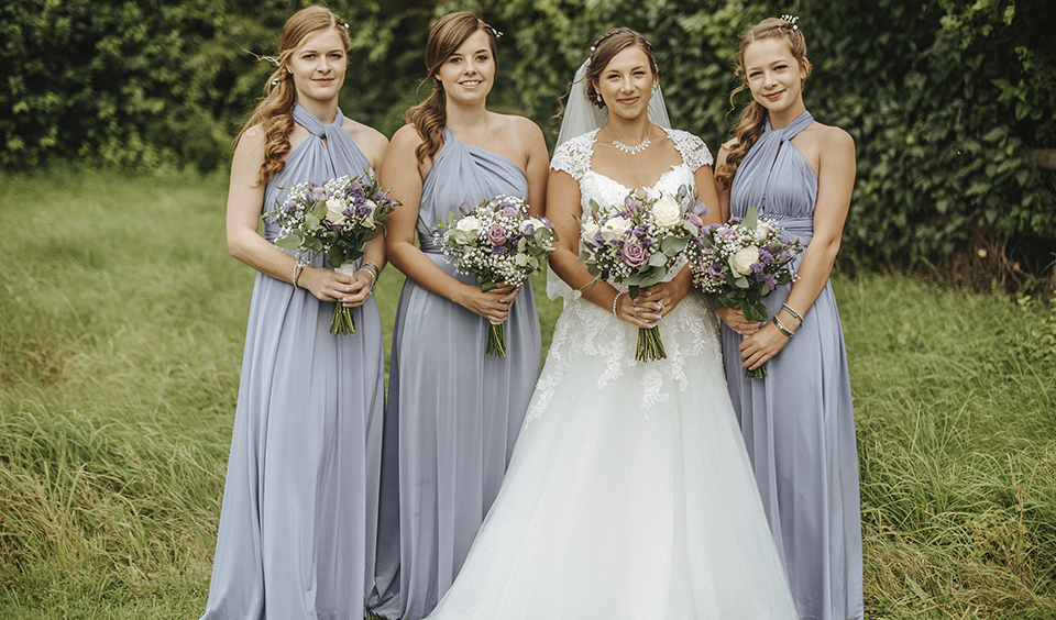 The bride stands with her bridesmaids who each wear floor-length blue grey multiway bridesmaid dresses