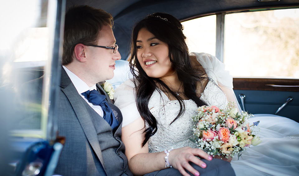 The bride and groom steal a moment away as they enjoy the comfort of their luxury wedding car