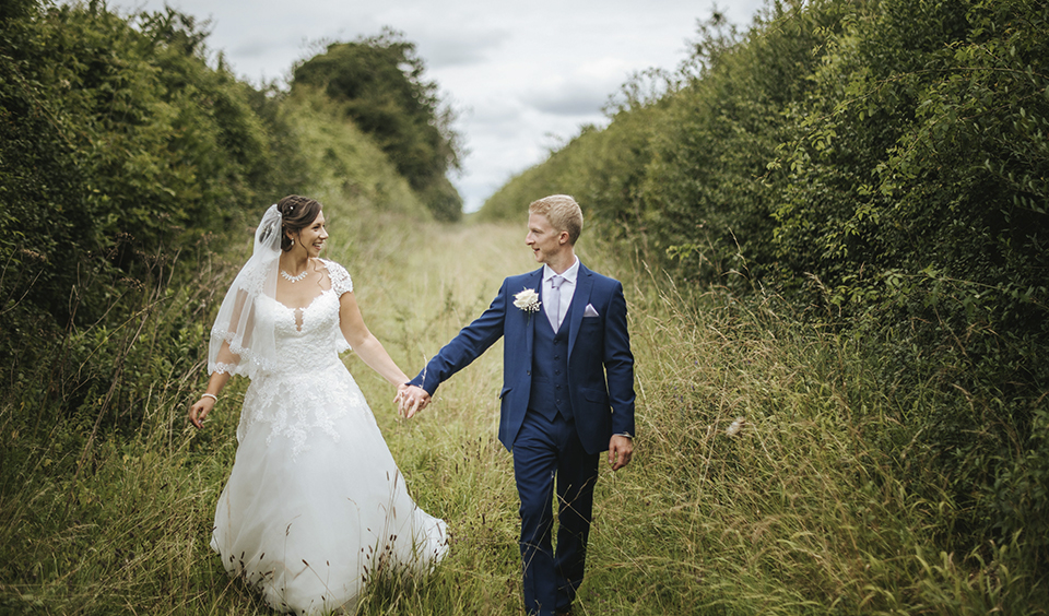 The couple enjoy the countryside setting whilst taking a stroll around the wedding venue hand in hand
