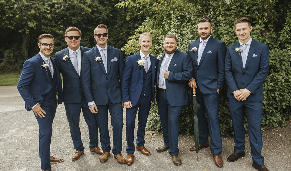 The groom stands with his groomsmen who each wear blue suits with blue ties and brown shoes