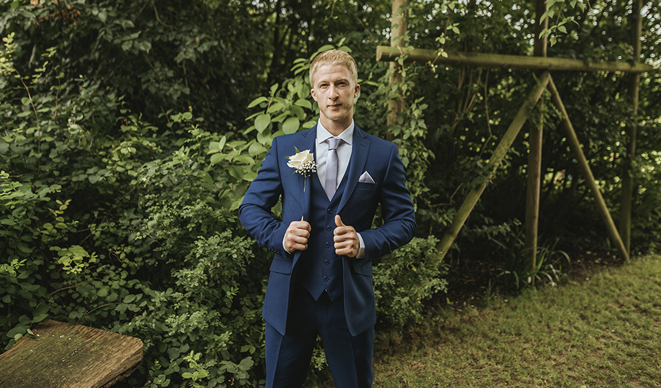 The groom wears a striking blue three-piece suit with a white flower buttonhole – wedding ideas