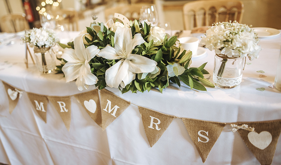 Mr and Mrs burlap bunting adorned the top table as well as beautiful floral arrangement of white lillies