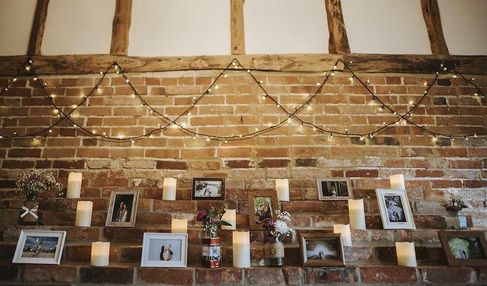 In the cosy and inviting Snug, the couple decorated the fireplace with photos in frames – wedding ideas