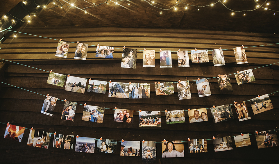 Photos of the couple with family and friends were hung from string against a wall in the barn – wedding ideas
