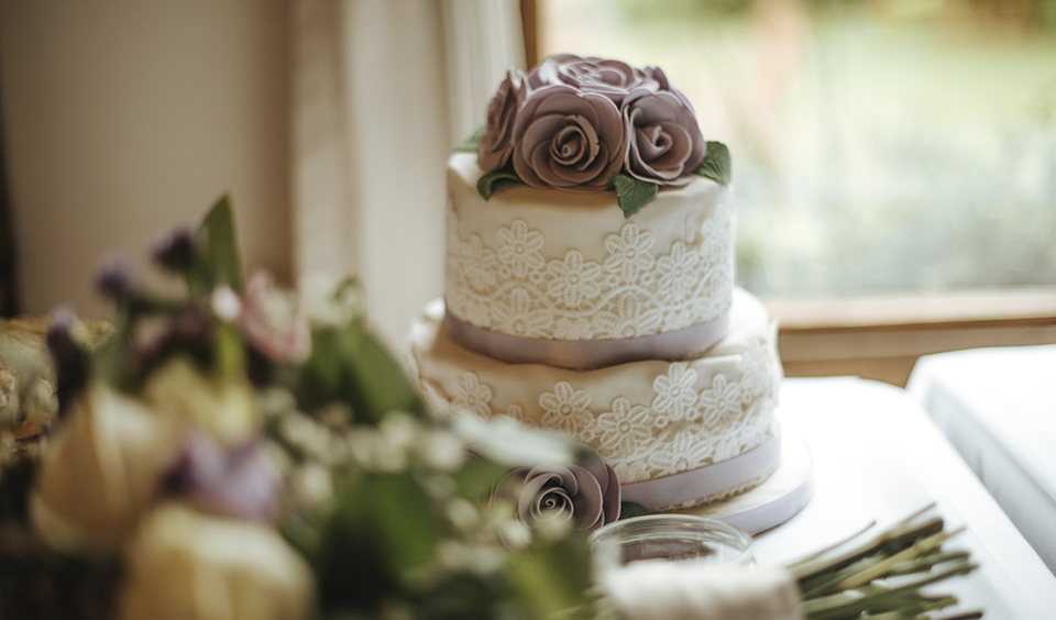 Another wedding cake consisted of two-tiers with iced lace detailing, purple ribbon and purple fondant flowers