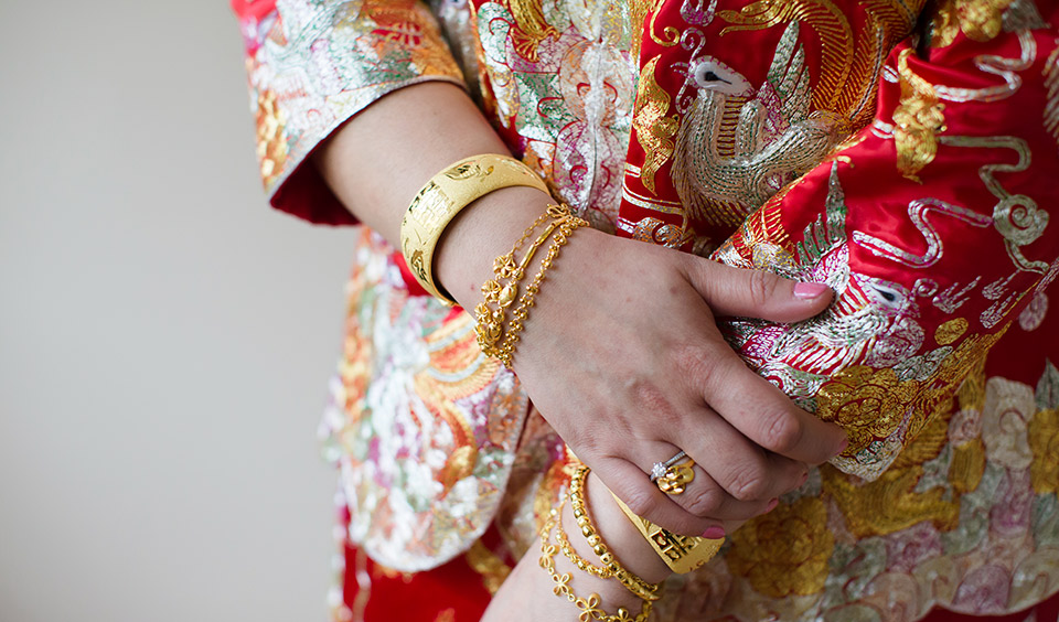 A close up of the bride's traditional Chinese dress and gold jewellery – Chinese wedding