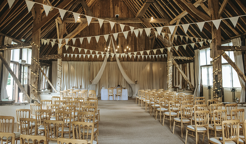 The beautifully rustic oak barn is the perfect space for a wedding ceremony with oak beams draped with bunting