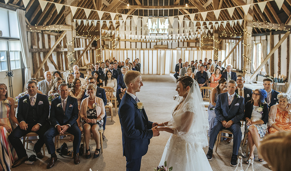 The bride and groom look at each other as they exchange their wedding vows in the spacious wedding barn