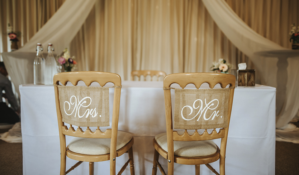 The wedding ceremony chairs for the bride and groom are decorated with burlap sashes that read Mr and Mrs