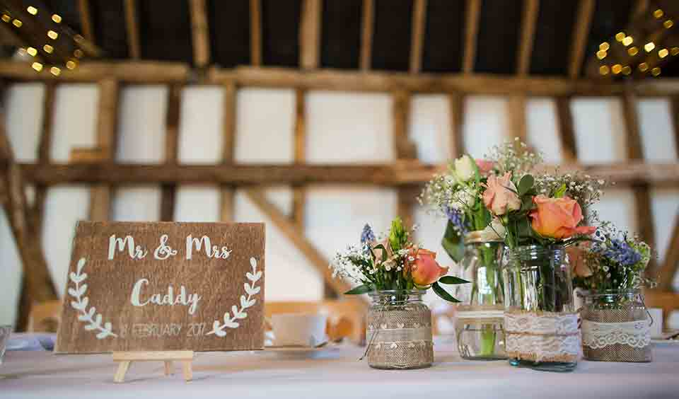 Tables were decorated with flowers in glass jars decorated with hessian and lace – wedding ideas