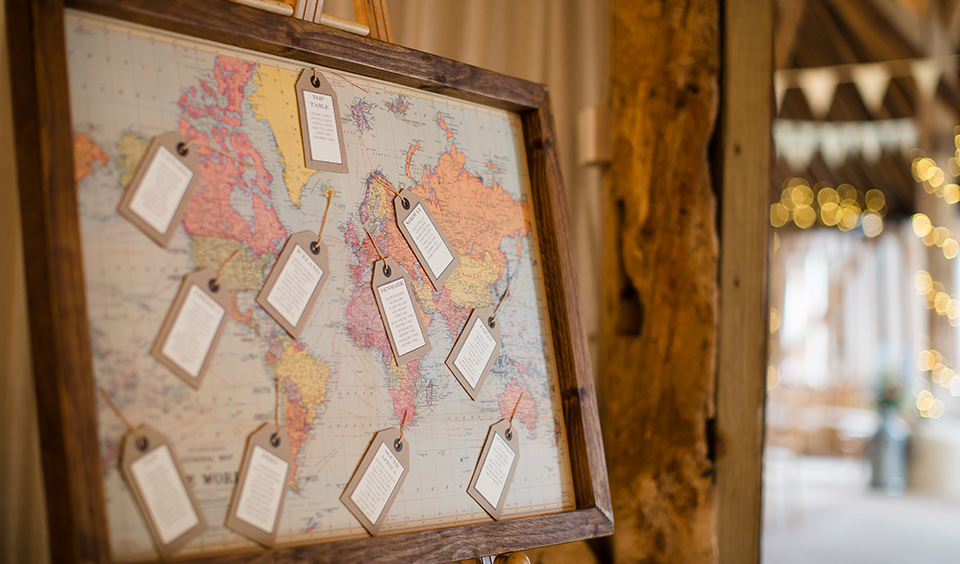 The couple's wedding table plan was displayed on a vintage world map and luggage tags – travel themed wedding