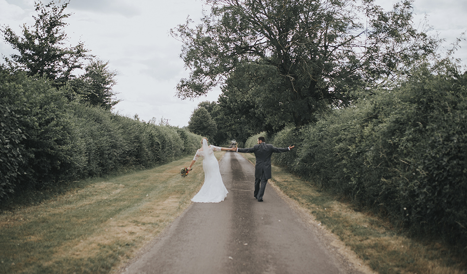 The bride and groom hold hands as they take a stroll at Clock Barn Hampshire