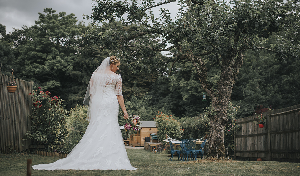 The bride enjoys a stroll in the gardens at Clock Barn Hampshire