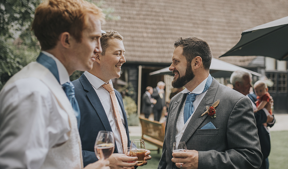 The groom enjoying a moment with wedding guests at Clock Barn in Hampshire