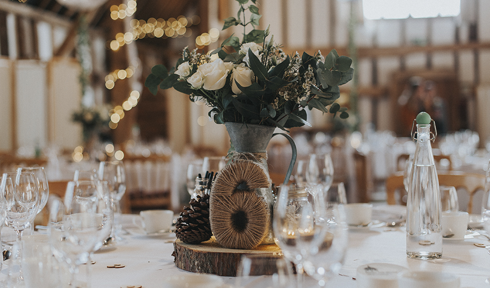 Create a wonderfully rustic table centrepiece by using eucalyptus leaves and some perfectly pale roses- wedding ideas