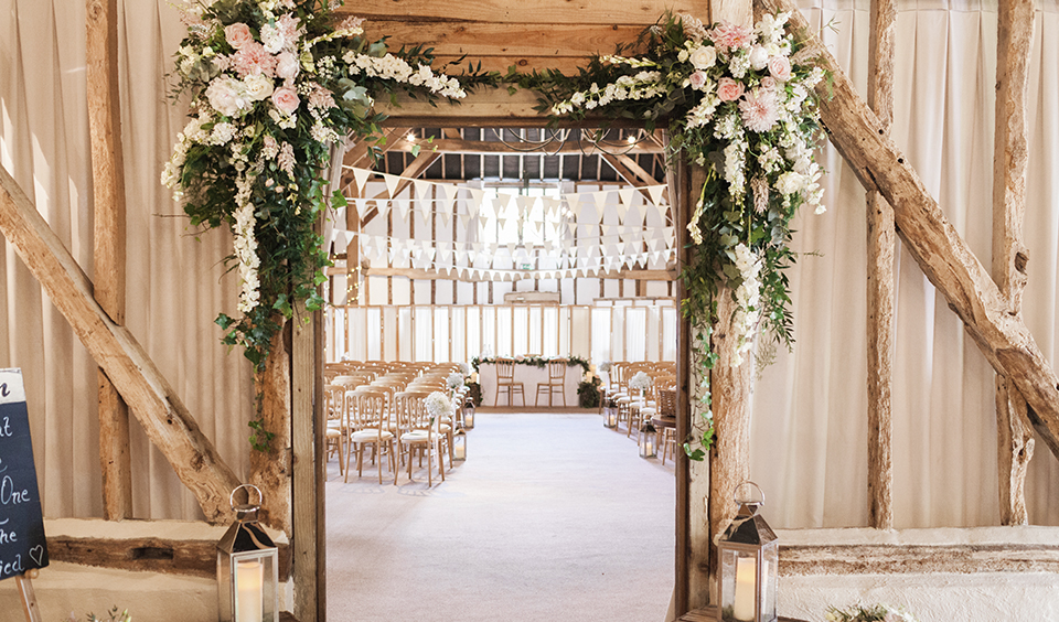 Decorate your barn wedding with beautiful arrangements of pale pink flowers and eucalyptus leaves trailing down the entrance to the barn