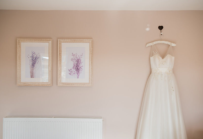 A bridal gown hangs in the Lavender Barn honeymoon suite after a stunning wedding at Clock Barn