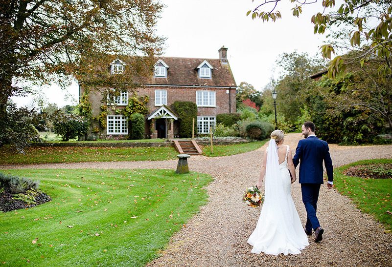 A bride and groom make their way up the path towards Tufton Warren Farmhouse wedding accommodation at Clock Barn