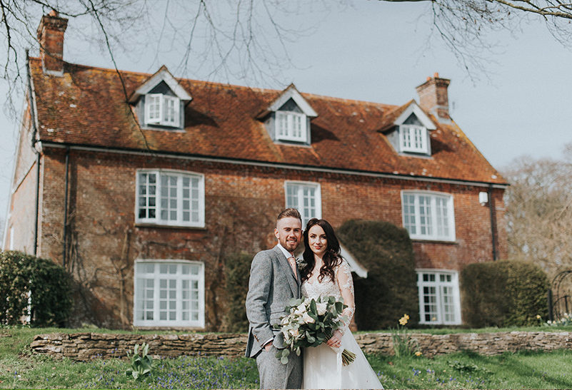 Newlyweds take a moment away from their guests for a wedding photo outside Tufton Warren Farmhouse at Clock Barn