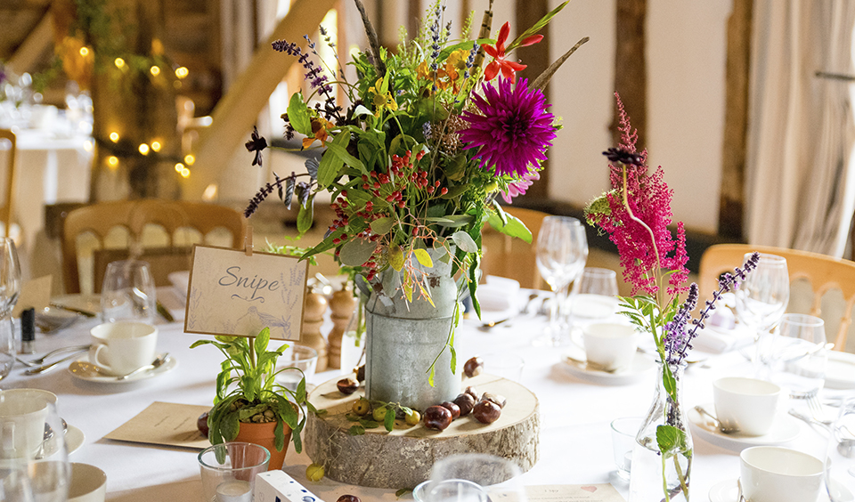 Decorate tables with seasonal flower centrepieces on natural log stands