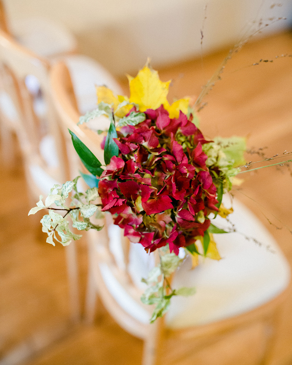 Seasonal flowers look beautiful attached to chairs to decorate the aisle