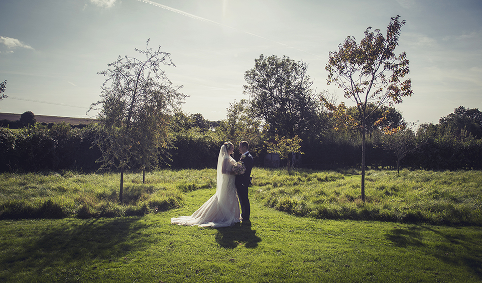 The newlyweds take a moment to pose for a photo in the garden at Clock Barn