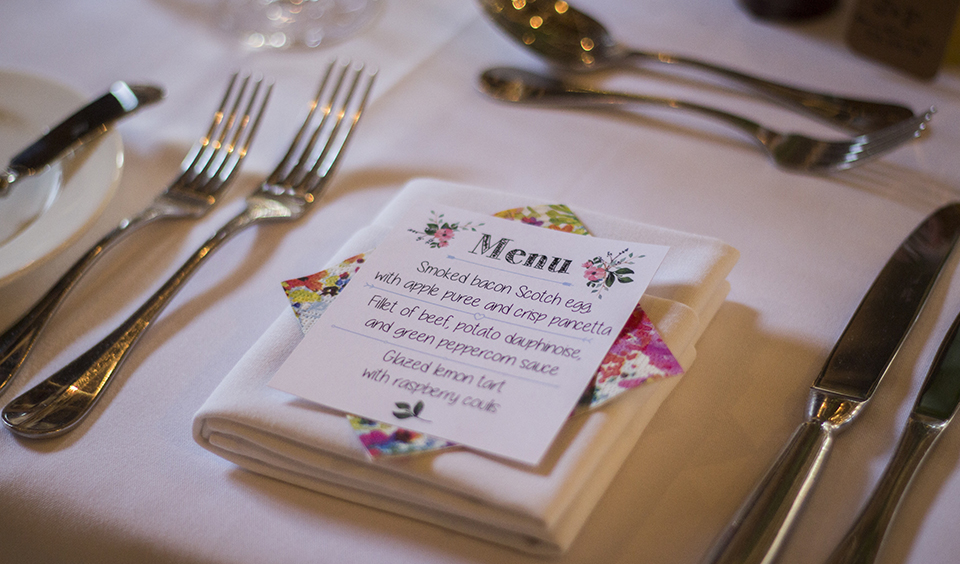 The bride handmade menus for each guest and displayed them on pretty floral napkins at this Clock Barn wedding