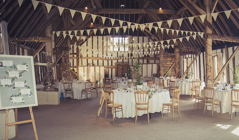 The tables were decorated with pretty potted wedding flowers with delicate bouquets tied to the odd chair at Clock Barn