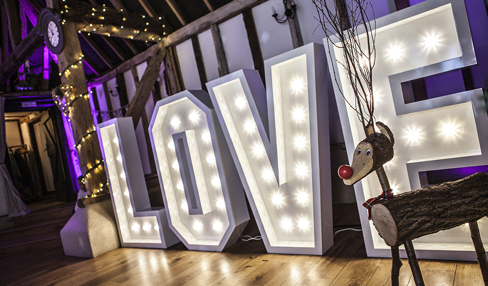 Large letter lighting is really effective to brighten your winter barn wedding at Clock Barn In Hampshire