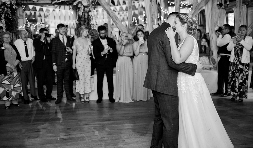 The happy newlyweds enjoy their first dance as their guests look on at Clock Barn in Hampshire